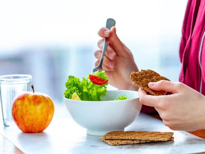 サラダとシリアルを食べる女性の手元