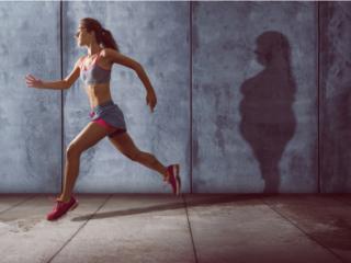 走り込みをする女性と壁に写った肥満女性のシルエット