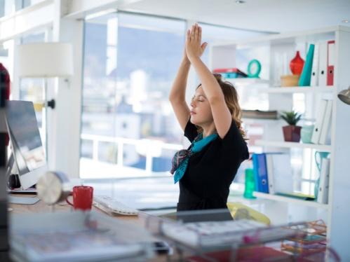 オフィスのデスクで腕を伸ばす女性