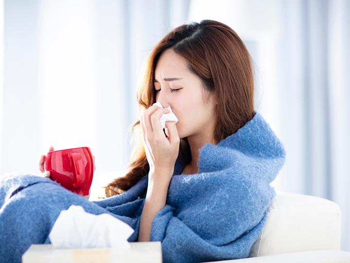 鼻をかんでいる女性のイメージ画像