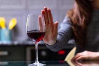 女性がワインの前に手を掲げ、飲酒を拒否している画像