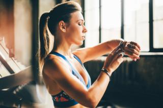 スポーティーな女性がスマートウォッチを見ている画像