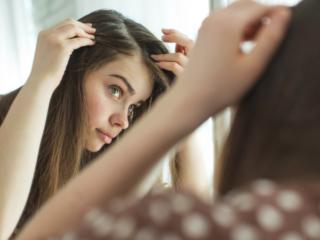 鏡で白髪をチェックする女性