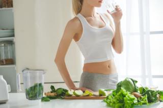 キッチンで野菜やフルーツをカットしながら水を飲んでいる女性