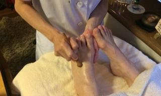 先生に指圧棒で足に刺激を受けている