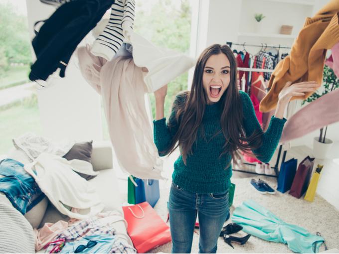 大量の服を放り投げる女性