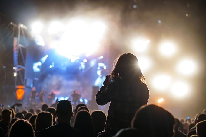 大人と一緒に夜のライブを楽しんでいる子どものイメージ画像