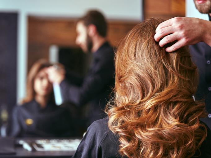 美容院で髪の状態を見てもらう女性