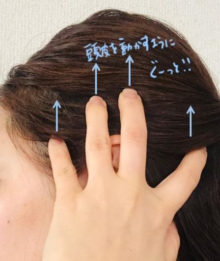 指を耳の上に置いている画像
