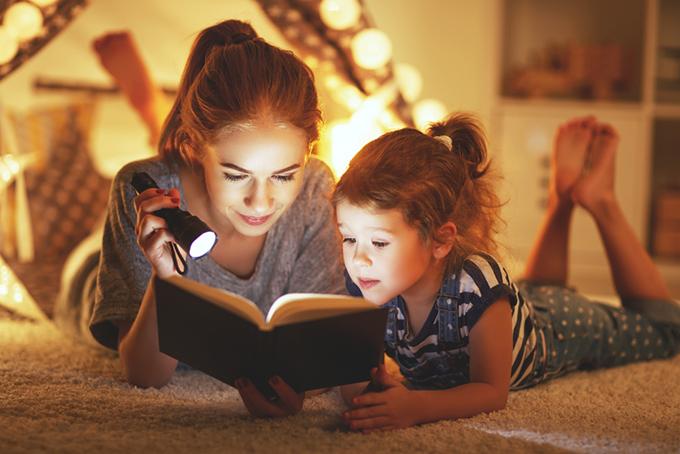 幼い女の子と母親が本を読んでいる画像
