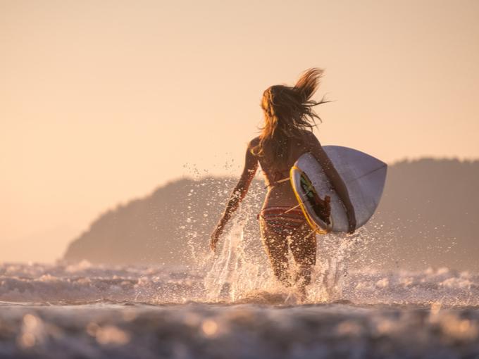 サーフィンをしに海に入る女性