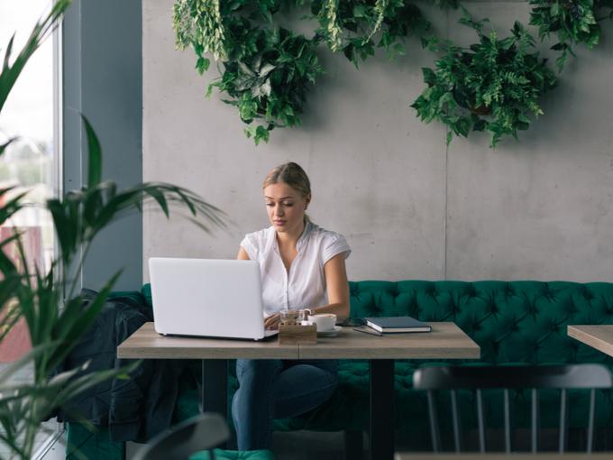 観葉植物など緑が多い室内で仕事をする女性