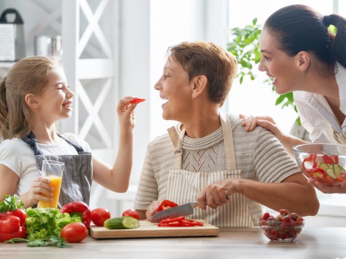 サラダを作る女の子と祖母と母親