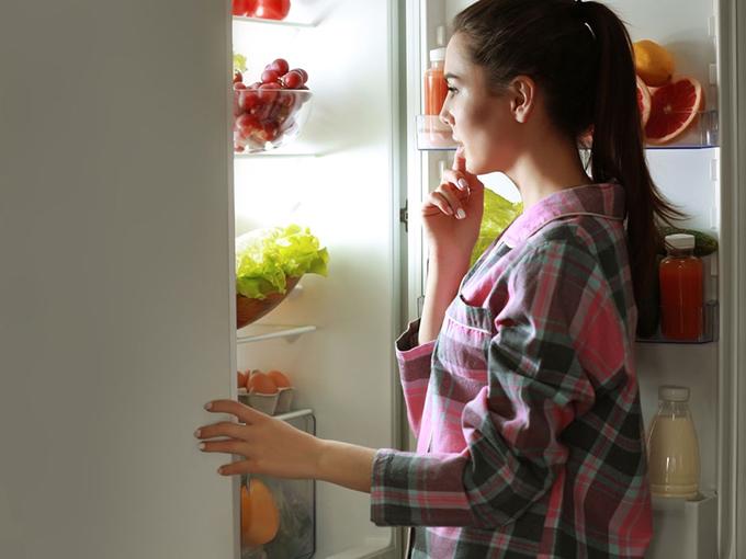 冷蔵庫の中を覗いている女性