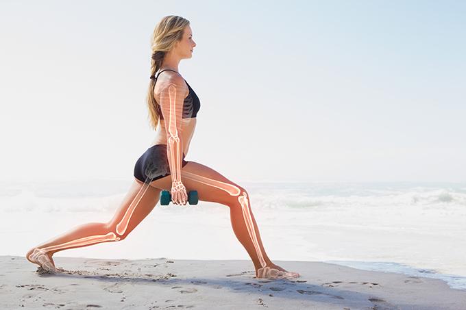 浜辺でストレッチする女性と透けて見える骨のイメージ