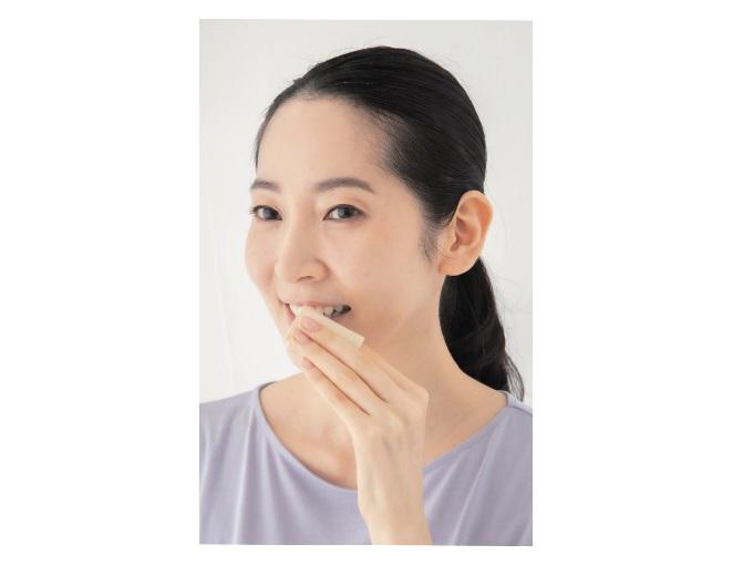 ガーゼで歯をふく女性
