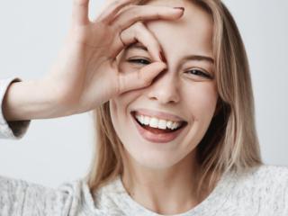 歯を見せて笑顔でOKサインをする女性