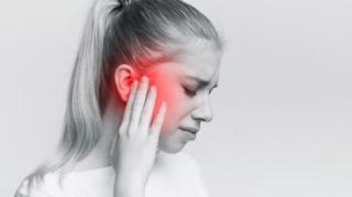 耳を痛そうに抑える女性の画像