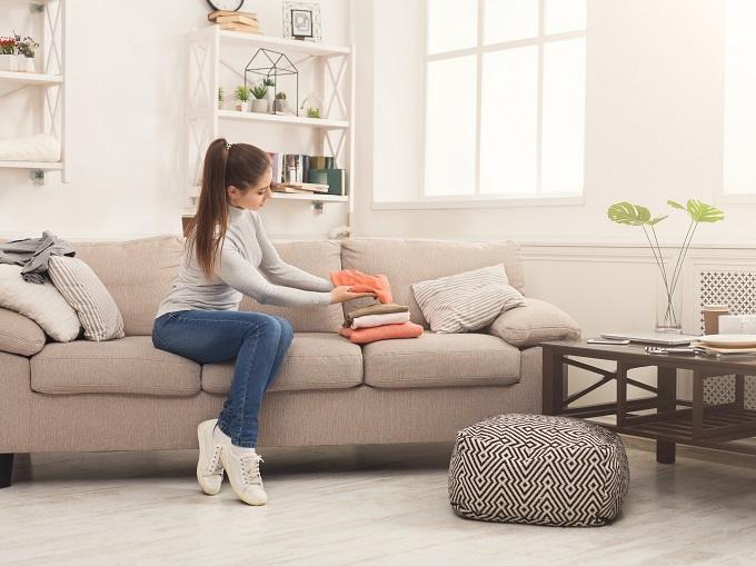 ソファに座って服をたたんでいる女性