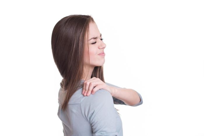 肩を痛そうに触る女性の画像