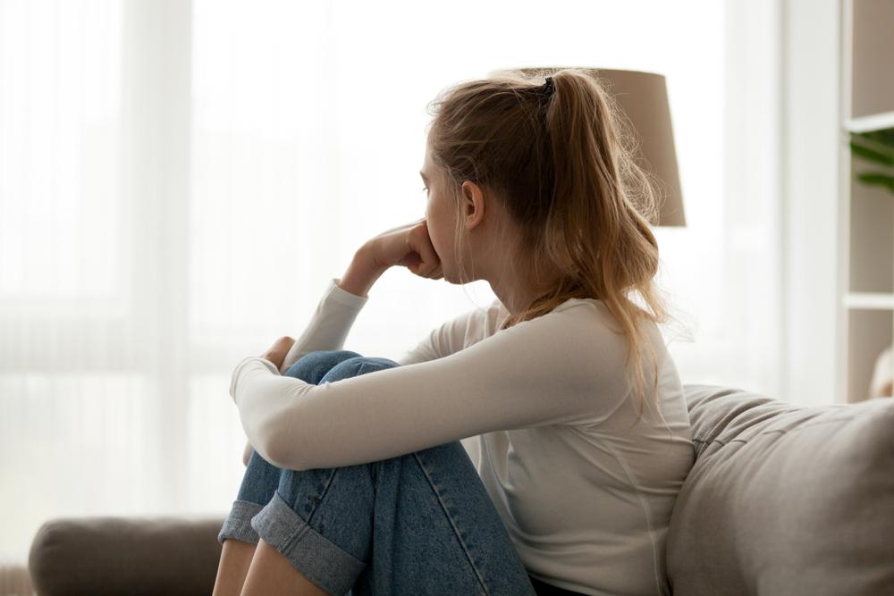 ソファに座り、落ち込んでいる女性