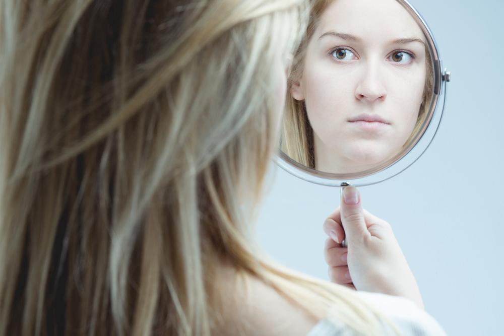 鏡をのぞき込む女性の写真