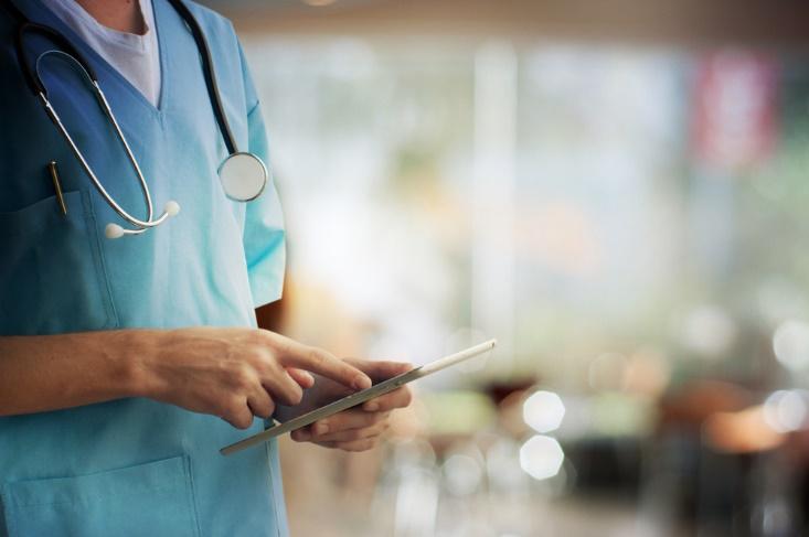 タブレットを使用する医師の手元画像