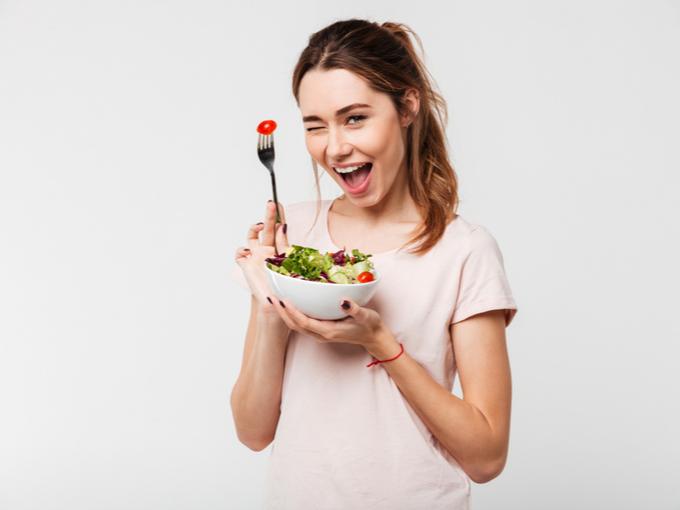 サラダを手にしてウィンクする女性