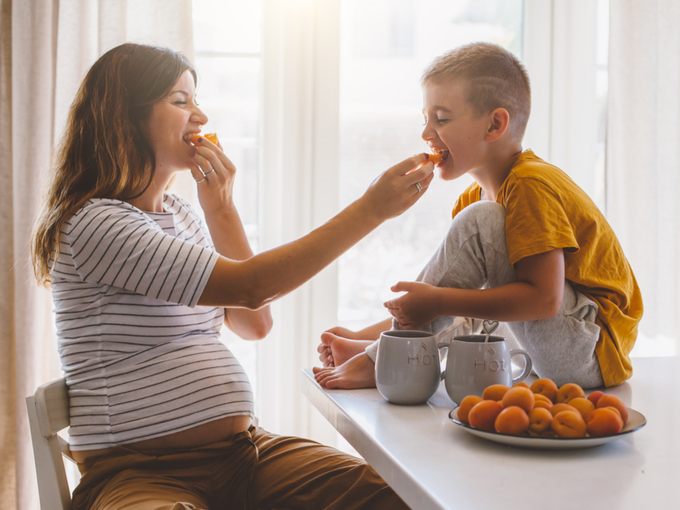 子どもと一緒にフルーツを食べる妊婦