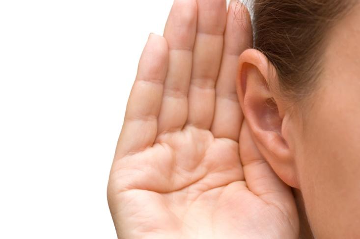 耳に手を当てている画像