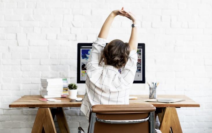 仕事中に伸びをしている女性