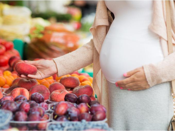 スーパーでフルーツを選ぶ妊婦