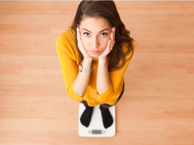 体重計にのって困った表情をする女性
