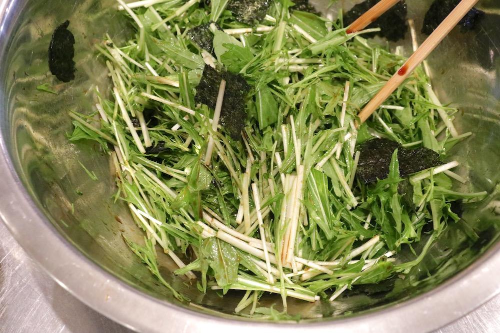 ボウルに入った水菜とのりを調味料と合わせて混ぜている