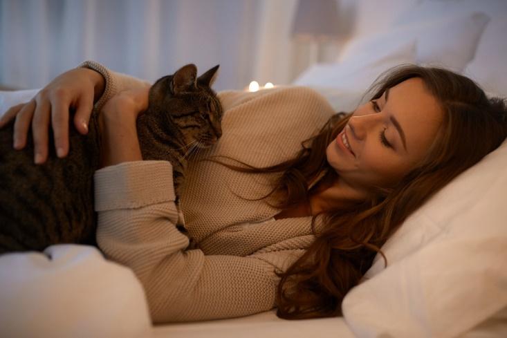 ベッドの上でねこと過ごしている女性