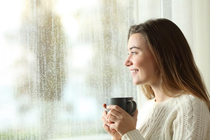 窓の外をながめるカップを持った女性の画像