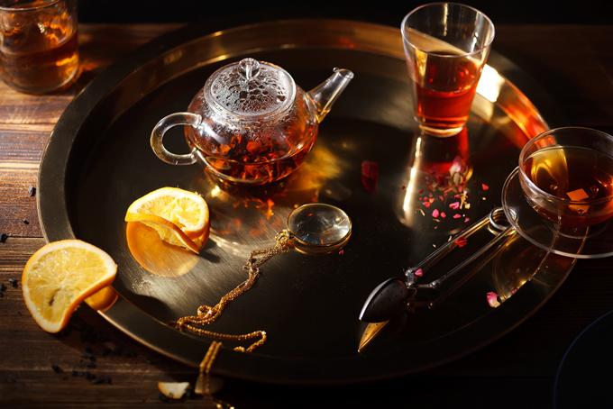 暗い部屋でいれた紅茶ポットとグラスに入った紅茶