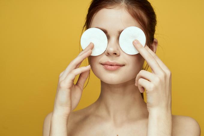 目もとに丸いコットンを当てている女性のイメージ画像