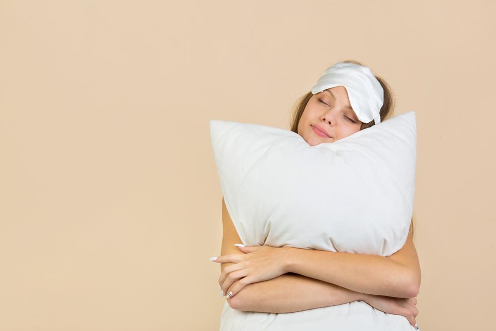 枕を抱えて笑顔の女性