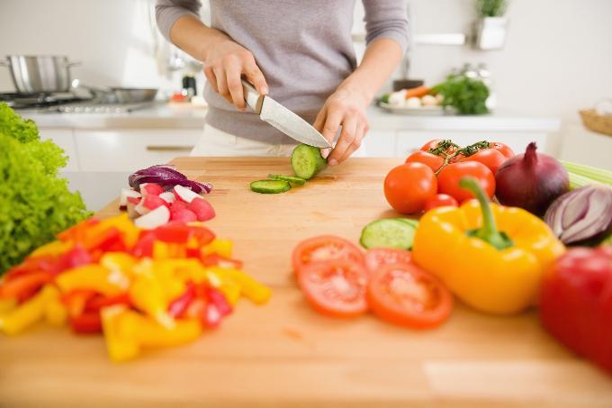 キッチンで野菜を切る人の手元