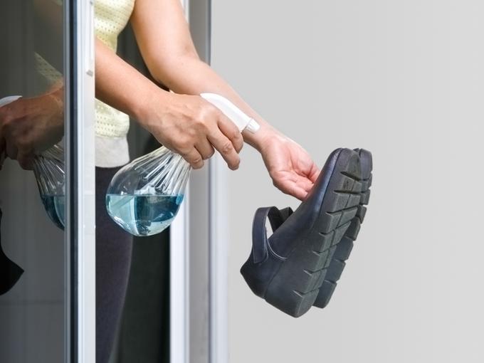除菌スプレーを靴にかける人