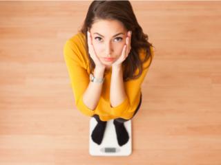 体重計にのって困った表情の女性