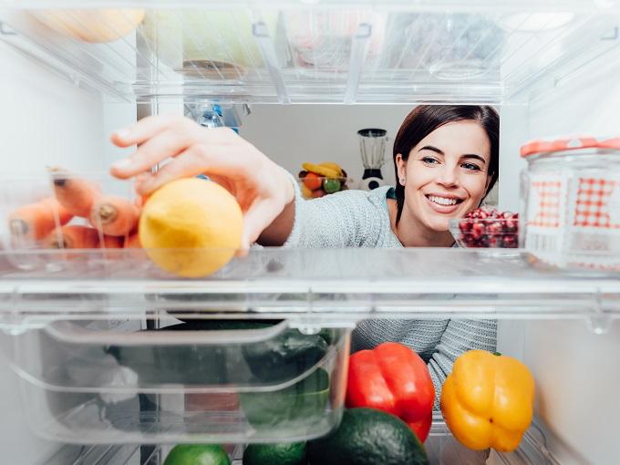 冷蔵庫から食べものをとっている女性