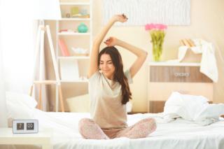 夜眠った後に目を覚まして伸びをしている女性