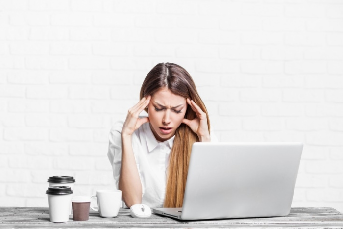 PCの前で頭を抱える女性の画像