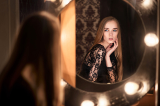 鏡みを見ている髪の長い女性