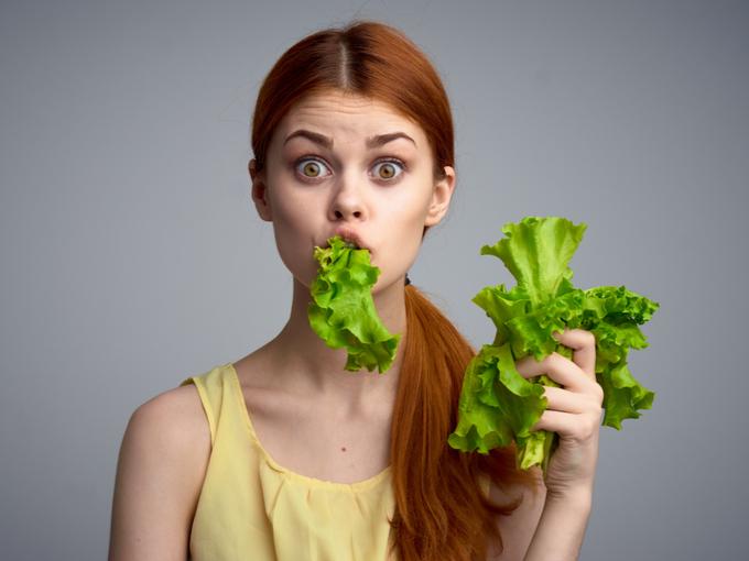 野菜を口にくわえたまま驚いた表情の女性