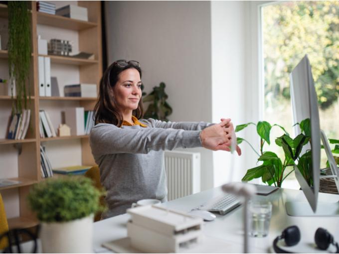 仕事の合間に腕を伸ばす女性