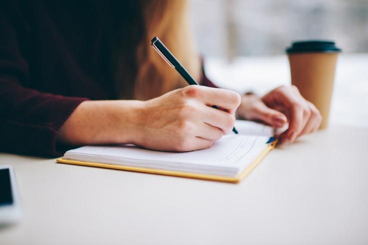 ノートに何か書いている女性画像
