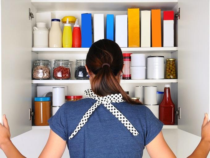 キッチンの収納場所を見ている女性のうしろ姿